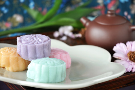 Colorful snow skin mooncake on plate with tea pot on background Stock Photo