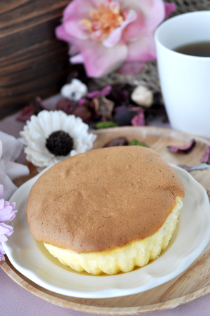 homemade cake: Sponge cake serving on plate with tea cup and floral on background