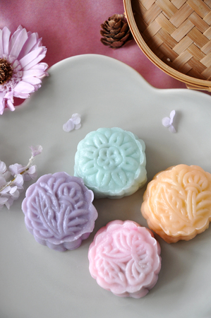 Above of snow skin mooncake on plate with flower on background Stock Photo