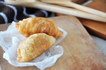 Two curry puff on wooden cutting board