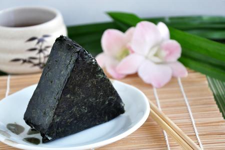 Onigiri on dish with chopstick on bamboo mat