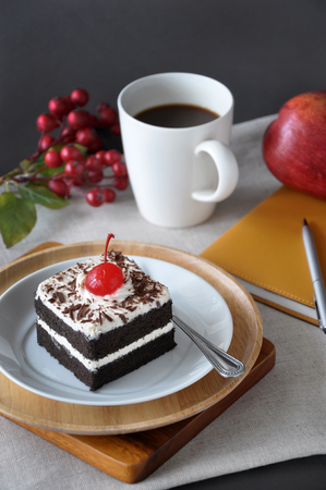 Piece of black forest cake with cup of coffee and notebook on background