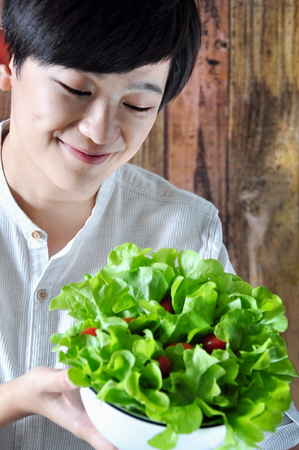korean salad: Asian young woman looking at her salad bowl with happy face