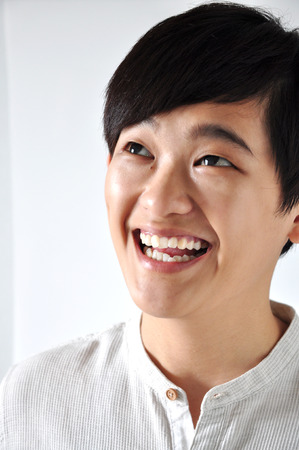 Young Asian woman looking up on white space with happy face