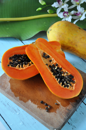 Half of fresh papaya on wooden cutting board Stock Photo