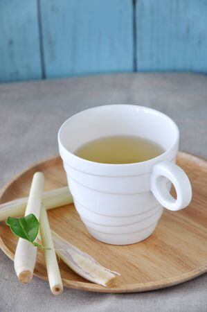 White mug of lemongrass tea put on wooden tray Stock Photo