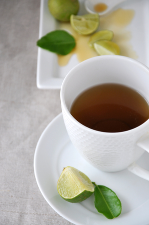 A cup of hot tea with lime and honey on background