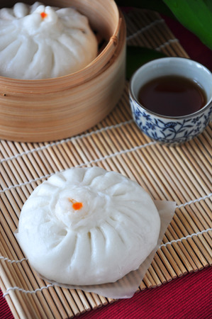 Steamed pork bun on bamboo mat with cup of tea