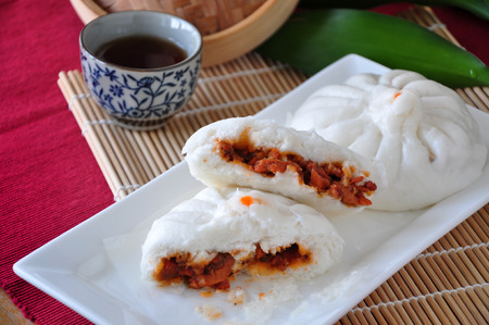 Half of Siopao show stuff of red pork inside on white plate with tea cup on background