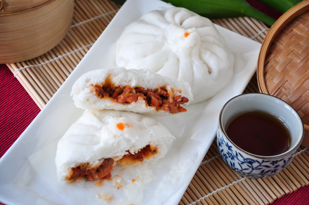 Pieces of half red pork bun on white plate
