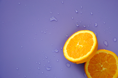 Cut half of fresh navel orange with splash water on purple background Stock Photo