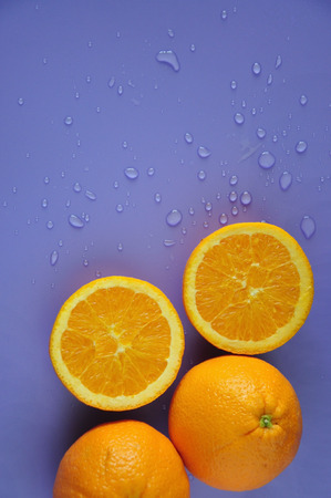 Top view of cut half pieces of navel orange with water drop on purple background with copysapce