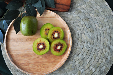Top view of red kiwifruit on wooden plate with copyspace