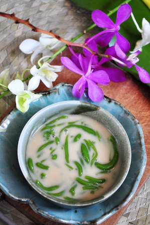 Above shot of traditional dessert Cendol serve in bowl with orchid decorated on background