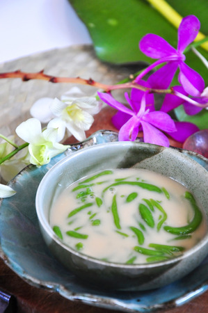 Bowl of Cendol traditonal dessert with orchid decorated on background