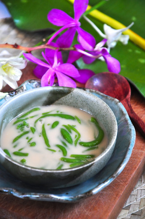 Traditional dessert Cendol serve in bowl decorated with orchid on background Stock Photo