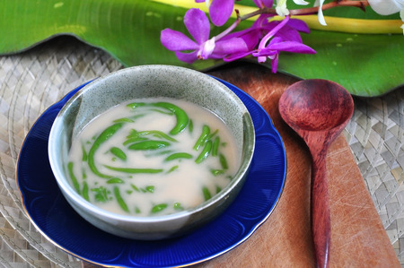 Bowl of Cendol traditional dessert put on wooden board with spoon