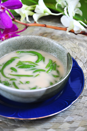 Close up bowl of Cendol traditional sweet with orchid on background
