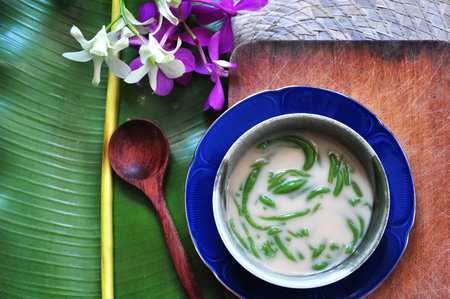 Cendol traditional dessert on wooden board with banana leaf and orchid on background  with space for text