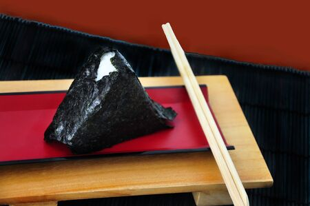 Onigiri Japanese rice ball on red plate with chopstick