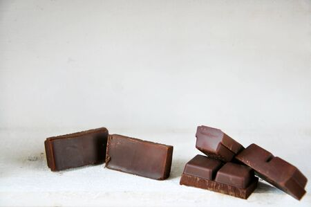 Dark chocolate bars on white wooden background with copy space