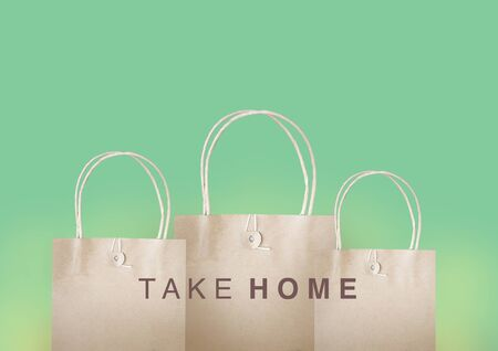 Take home message on three paper bags with pastel green background