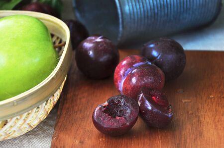 Close up fresh juicy plum cut half put on wooden board Stock Photo