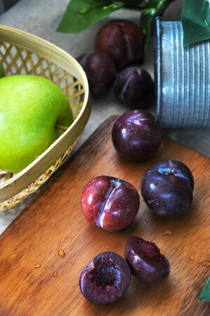 Close up fresh plum on wooden board with apple on background Stock Photo