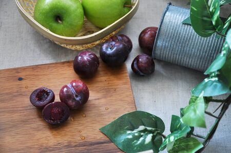 Fresh fruits plum from tin and green apple in basket put on natural concpet background with space for text Stock Photo