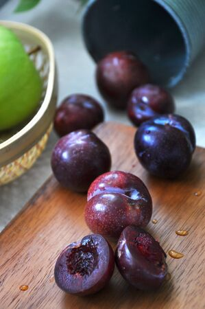 Fresh plum on wooden board with green apple on background