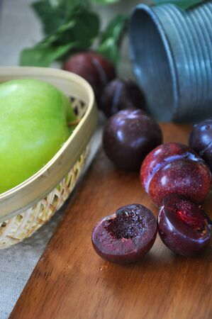 Piece of juicy plum on wooden board background