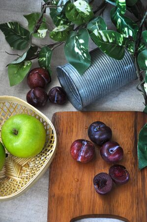 Top view of fresh plum on wooden board with green apple in basket decorated with green leaves  on background