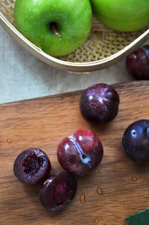 Top view of fresh plum on wooden board with green apple on background