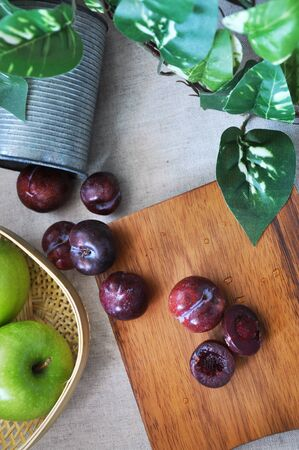 Top view of fresh plum on wooden board decorated with green leaves and fresh apple with space for text on background Stock Photo