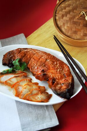 Whole piece of delicious Chinese barbecue pork on dish with copyspce on red background Stock Photo