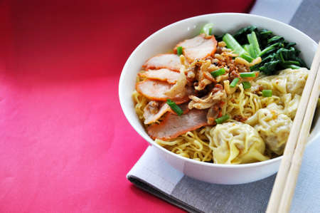 Big bowl of egg noodles with wonton and sliced grilled pork on red background with copy space Stock Photo