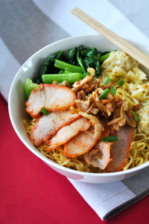 Close up big bowl of egg noodles with grilled sliced pork and wonton put on red background Stock Photo