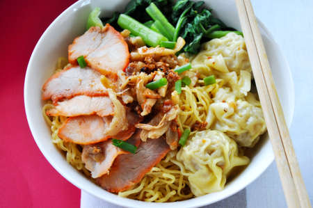 Top view of delicious egg noodles with sliced pork and wanton in big bowl