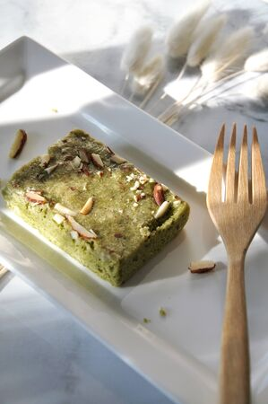 Lighting on matcha green tea brownie serving on white plate with wooden fork on white background with copy space