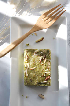 Top view of matcha fudge brownie on white plate with wooden fork on background