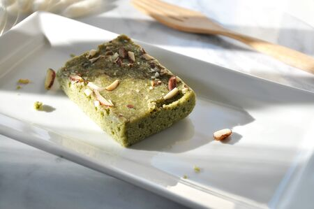 Window light on matcha green tea brownie on white plate with sapce for text on background