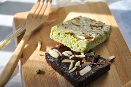 Close up piece of matcha brownie and dark chocolate brownie on wooden board