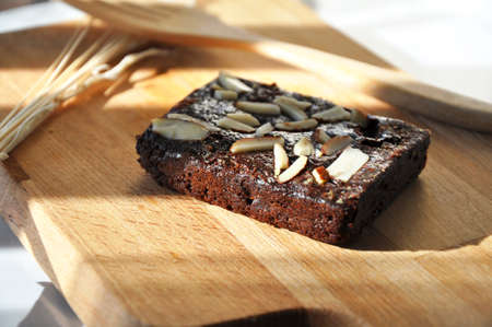 Light and shadow on fresh baked fudge brownie put on wooden board