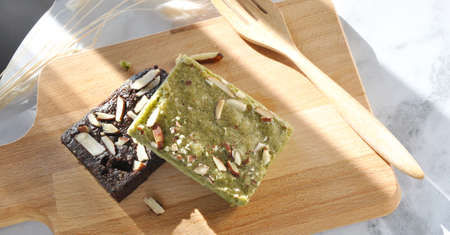 Healthy matcha and dark chocolate brownie on wooden board Stock Photo
