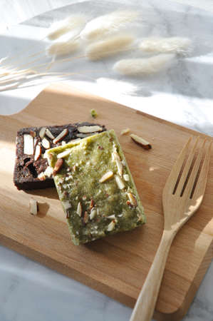 Matcha green tea brownie and chocolate brownie on wooden board with copy space on white background