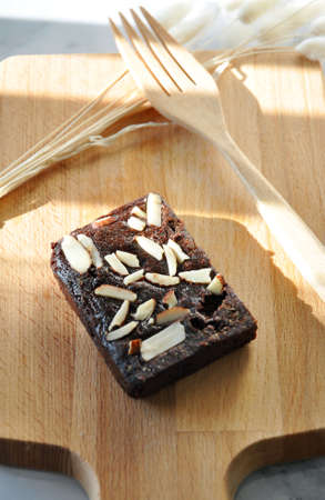 Dark chocolate fudge brownie top with sliced almonds put on wooden board Stock Photo