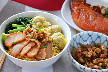 Big bowl of egg noodles with sliced pork and wanton with grilled pork dish on background Stock Photo