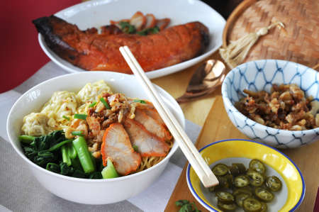 Lunch set of Chinese food wanton mee with whole piece of red grilled pork on background