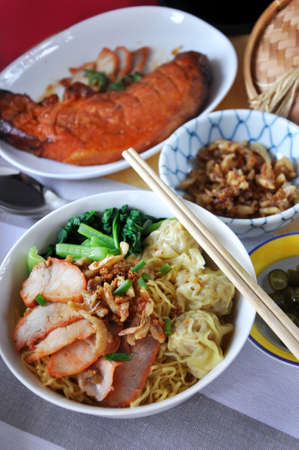 Top view of Chinese food set of wanton egg noodles and red grilled pork on background