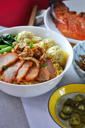 Bowl of delicious wanton mee grilled pork for lunch  with copy space on background Stock Photo